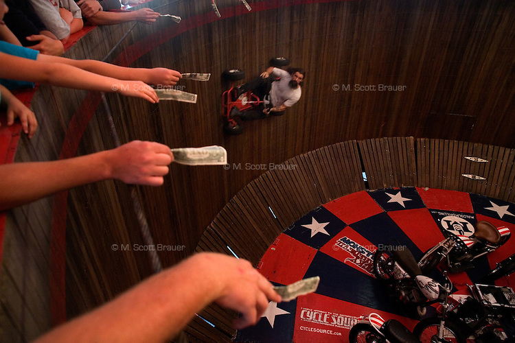 Members of the audience hold out dollar bills for stunt riders to grab during the performance of the Wall of Death traveling show at Evel Knievel Days in Butte, Montana, USA.