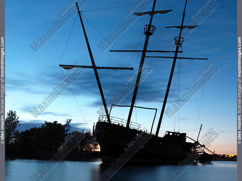Grounded tall ship silhouette against twilight sky