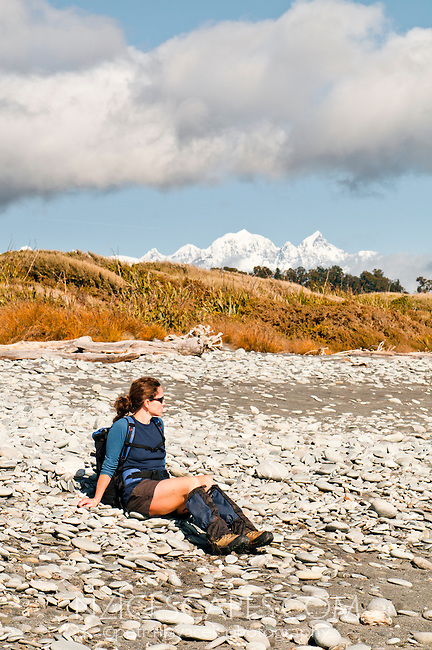 Female hiker on Three Mile Beach near Okarito. Southern Alps in view, Westland National Park, West Coast, New Zealand