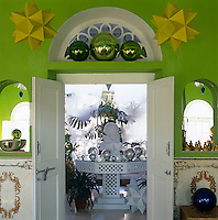 A doorway flanked by a pair of vivid yellow polyhedra leads from the lime-green study to the veranda