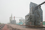 Metal grain elevators by the railroad tracks, rain
