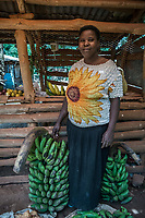 Uganda, Wamala. Teddy Kalema and her husband Charles, cooking on the Biolite cook stove in their home. This system also charges a light and their mobile phone. Teddy in her fruit and vegetable shop.