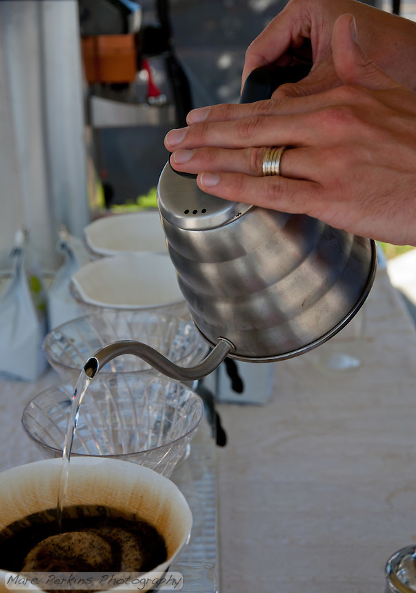 Portola Coffee Lab's barista hand-pours water onto freshly-ground coffee beans at South Coast Collection's Farmers' Market.