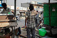 A young boy drinks water from the food stall at the main square in the summer heat in Medak, Telangana, India.