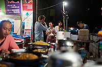 Food stands serve customers outside outside the B District Middle Gate of Chongqing University in the Shapingba district of Chongqing, China. Xie Guang Rong has run one stand, which serves tu dou ni, jiaozi, and other small snacks, for 11 years there. They chose the location directly outside the university gate because it's such a high traffic areas. She said that the stand is popular with students because prices are low and the portions she serves are big. A large helping of tu dou ni, for instance, costs 3RMB. She and her husband rent the stall space from the surrounding community.