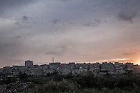 Sheik Maksoud neighborhood is seen at the dusk from the bank of the Quelq river after several days of heavy fighting and shelling that have forced thousands of residents to flee into safe areas outside Aleppo City.
