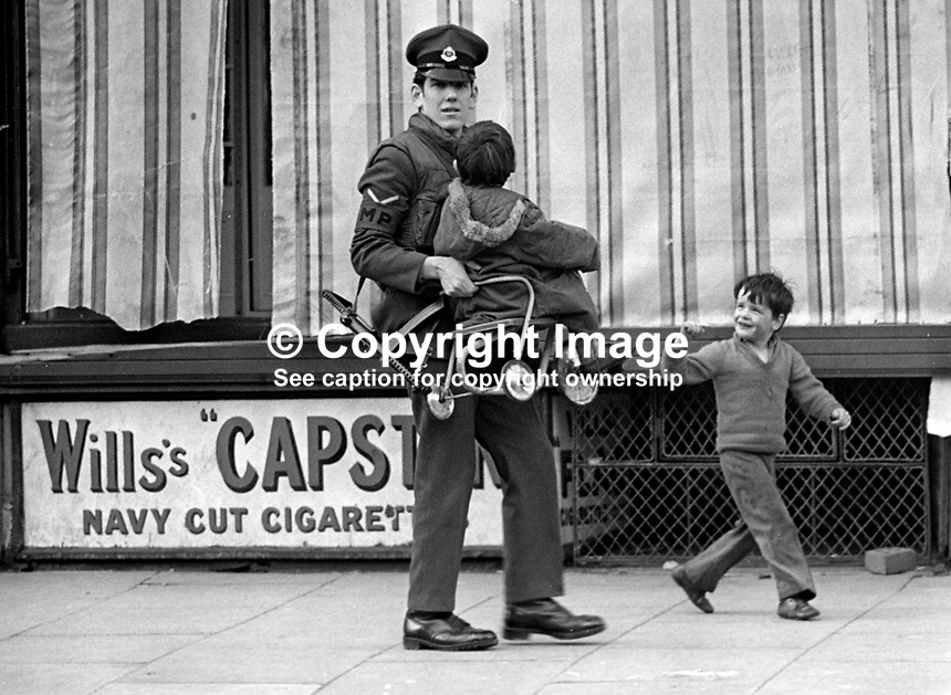 British Army Military Policeman carries a child and its tricycle away from danger following an explosion at a Co-operative Store, Belfast, N Ireland, UK. A second child is also escorted away. A second bomb at the store was subsequently defused. NI Troubles.  Ref: 19720300001.<br /> <br /> Copyright Image from Victor Patterson, 54 Dorchester Park, Belfast, UK, BT9 6RJ<br /> <br /> t1: +44 28 9066 1296<br /> t2: +44 28 9002 2446<br /> m: +44 7802 353836<br /> <br /> e1: victorpatterson@me.com<br /> e2: victorpatterson@gmail.com<br /> <br /> www.victorpatterson.com<br /> <br /> IMPORTANT: Please see my Terms and Conditions of Use at www.victorpatterson.com