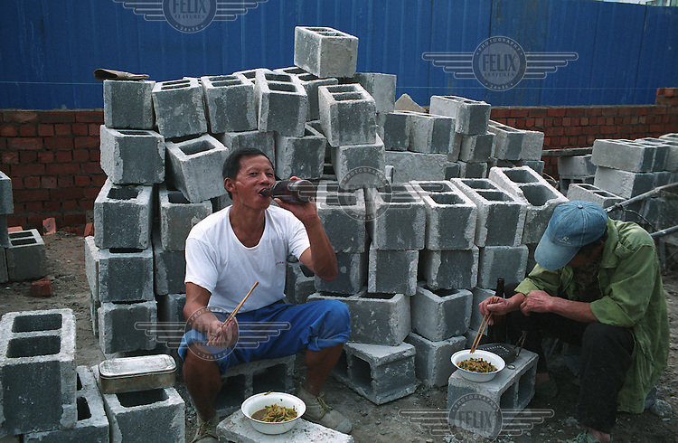 Two workers take a lunch break on a road expansion site, part of the redevelopment project for the upcoming 2010 World Expo in Shanghai.