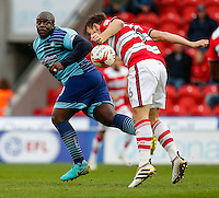 Adebayo Akinfenwa of Wycombe Wanderers beats Andrew Butler of Doncaster Rovers to the ball during the Sky Bet League 2 match between Doncaster Rovers and Wycombe Wanderers at the Keepmoat Stadium, Doncaster, England on 29 October 2016. Photo by David Horn.