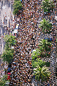 Rio de Janeiro, Brazil. Street carnival: mass of people dancing on the street with palm trees and iconic mosaic design of the Ipanema pavement viewed from above.