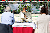 First mass in two months celebrated in the church of Santissimo Sacramento, in the south-east district of Rome. As the measures of social distancing would allow few faithfuls inside the church, the priest, Don Maurizio Mirilli celebrates the mass in the adjacent football field.<br /> Roma May 18th 2020. Covid-19 Italy further relaxes lockdown. Today a Council of Minister's decree will allow almost all the activity to reopen. Clothes shops, shopping centers, hairdresser and churches for religious services. <br /> Photo Samantha Zucchi Insidefoto