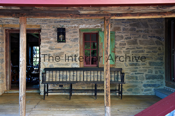 A long black bench has been placed on the back porch which connects the front house with the stone outbuilding