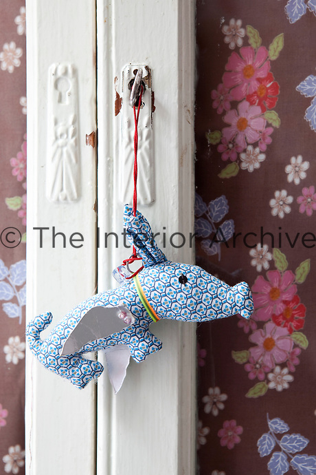 A whimsical fabric toy hangs from a cupboard in a child's bedroom and the doors are covered in a flowered fabric
