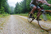 Man biking on Rob Brook Road in Albany, New Hampshire USA. This dirt road follows parts of the old Bartlett and Albany Railroad.