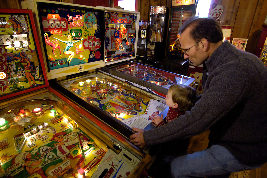 Chuck Hoskins and his son Blaze, 3, play a pinball game at the Arcade in Manitou Springs, CO. Michael Brands for The New York Times.