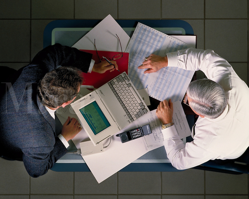 Two businessmen go over plans and schedules. Overhead view. Little Rock, Arkansas.