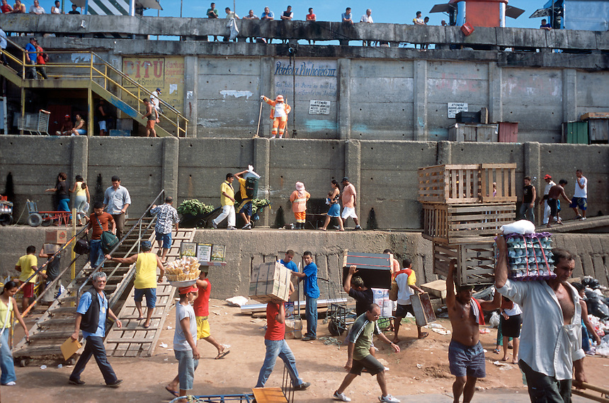 Porters, boat passengers and market vendors crawl over the walls of the port along the beach of the Rio Negro in Manaus, Brazil, Friday, Jan. 9, 2006. With few roads leading to the outside world, most goods are brought to the city 1,000 miles inland from the coast by boat. (Kevin Moloney for the New York Times)