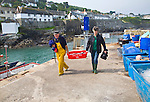 Man and women landing their fishing catch at the village of Coverack on the Lizard peninsula, Cornwall, England