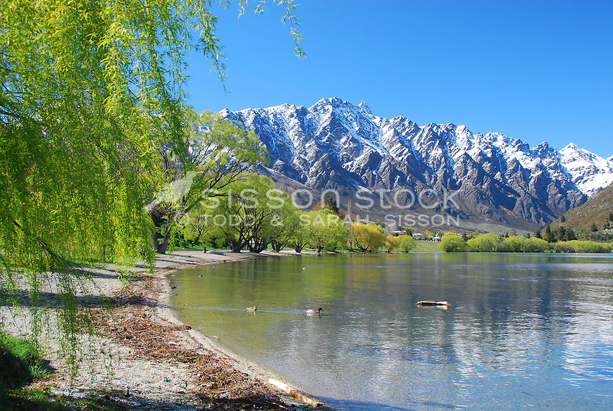 The Remarkables mountain range from the shores of Lake Wakatipu at Frankton, Queenstown, New Zealand | Green spring willows | Blue Sky