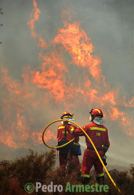 Members of the Spanish Army Emergency Unit (UME) try to extinguish a fire burning in La Zoma, on July 23, 2009 near Teruel. Some 500 people were battling another wind-fuelled wildfire in northeastern Spain which claimed the lives of four firefighters and seriously injured two others. Temperatures were forecast to reach 41 degrees Celsius (105 degrees Fahrenheit) in many parts of Spain on Wednesday, raising the risk that more wildfires could break out.  on July 23, 2009. (C) Pedro ARMESTRE