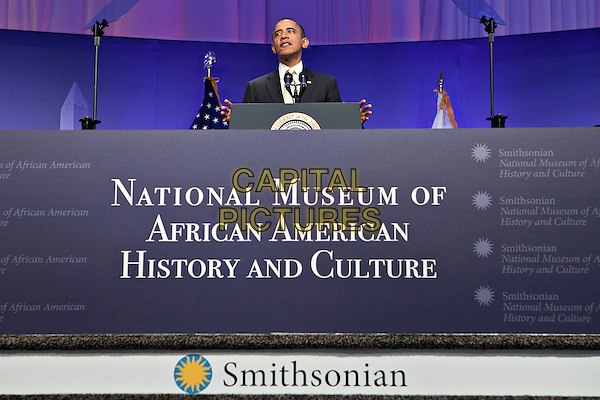 United States President Barack Obama speaks at the groundbreaking of the Smithsonian National Museum of African American History and Culture in Washington, D.C. on Wednesday, February 22, 2012. The museum is scheduled to open in 2015 and will be the only national museum devoted exclusively to the documentation of African American life, art, history and culture. .half length podium speech black suit  .CAP/ADM/AH.©Andrew Harrer/Pool/CNP/AdMedia/Capital Pictures.