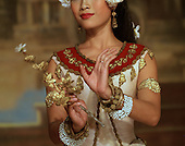 "Close up of Aspara Dancer's hands showing the bent-finger movements inherent in the Cambodian dance-style and the lower portion (nose and mouth only) of the dancer's face showng the ""fixed-smile"" worn by the dancers. The daner is holding a gold leaved want in her right hand and her arms are decorated with white and bold beads with a gold band on the upper right arm."