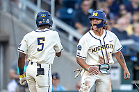 Michigan Wolverines outfielder Jordan Brewer (22) celebrates with teammate Christian Bullock (5) after scoring against the Vanderbilt Commodores during Game 1 of the NCAA College World Series Finals on June 24, 2019 at TD Ameritrade Park in Omaha, Nebraska. Michigan defeated Vanderbilt 7-4. (Andrew Woolley/Four Seam Images)