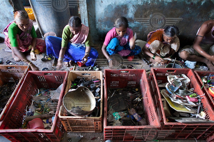 Women work at a recycling centre in Dharavi slum.