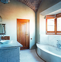 The white marble bathroom has a vaulted brick ceiling