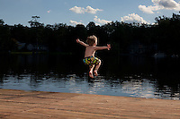 Little boy jumping off a summertime dock and into a public lake