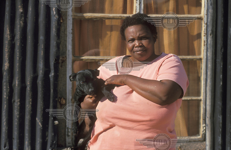 © Chris Sattlberger / Panos Pictures..Cape Town, South Africa...Woman with her pet dog, in the Kayelitsha township.