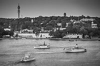 Tre båtar på Stockholms ström med Djurgården och Kaknästornet i bakgrunden i svartvitt
