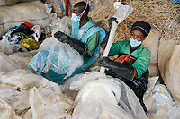 RWANDA, Kigali, plastic recycling at company ecoplastics, worker sort, clean and dry plastic foils before processing to granulate which is used for new plastic products / RUANDA, Kigali, plastic recycling bei Firma Ecoplastics, Sortierung, Reinigung und Trocknung von alten Folien bevor sie zu Granulat recycelt werden