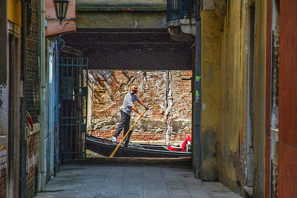 Gondolier framed by buildings, Venice, Italy.