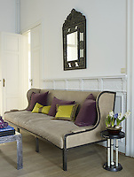 A Casamidy designed sofa covered in satin cushions runs the length of one wall in the living room beneath a carved French mirror