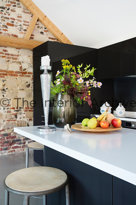 The kitchen features an island on wheels, which can be used as a breakfast bar or serving station. The stools are vintage. The original stone and brick walls of the barn have been kept exposed and adds a lovely texture to the room.