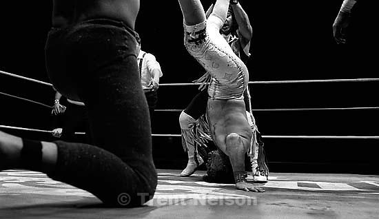 Wrestling action at Luche Libre pro-wrestling. guy covered in blood<br />
