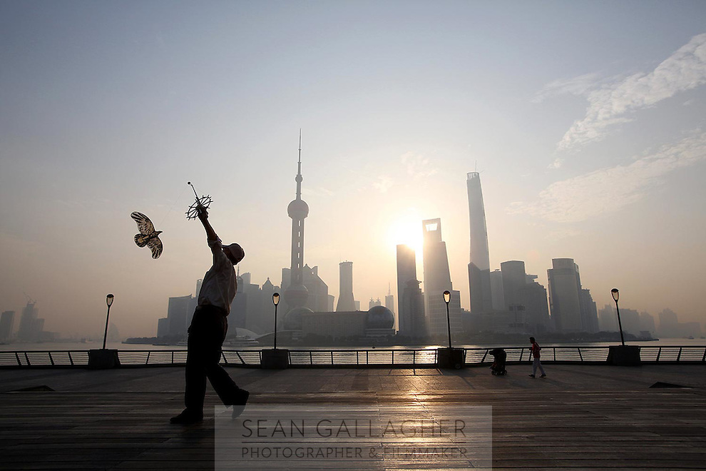 A man flies a paper kite at sunrise in front of the distinctive Pudong skyline, 2014.<br />