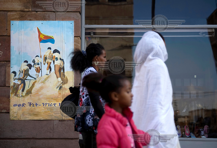 People walk by a poster on a wall showing Eritrean soldiers during the liberation struggle. ..