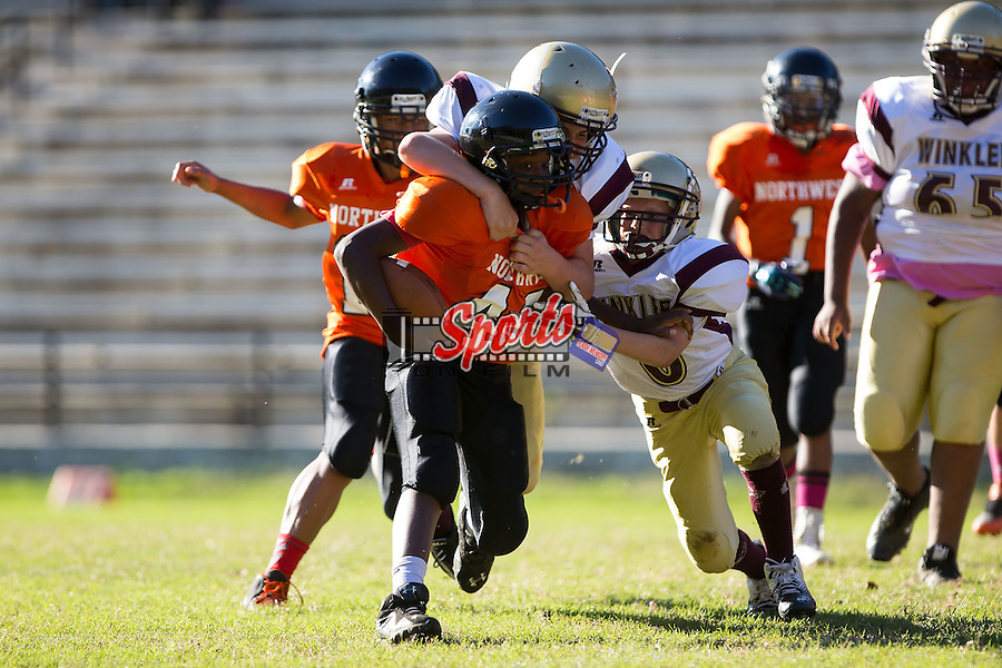 Michael Steele Jr. (48) of the Northwest Cabarrus Titans is chased by #63 of the Winkler Wolves in 7th grade football action at Trojan Stadium October 7, 2014, in Concord, North Carolina.  The Titans defeated the Wolves 58-30.  (Brian Westerholt/Sports On Film)
