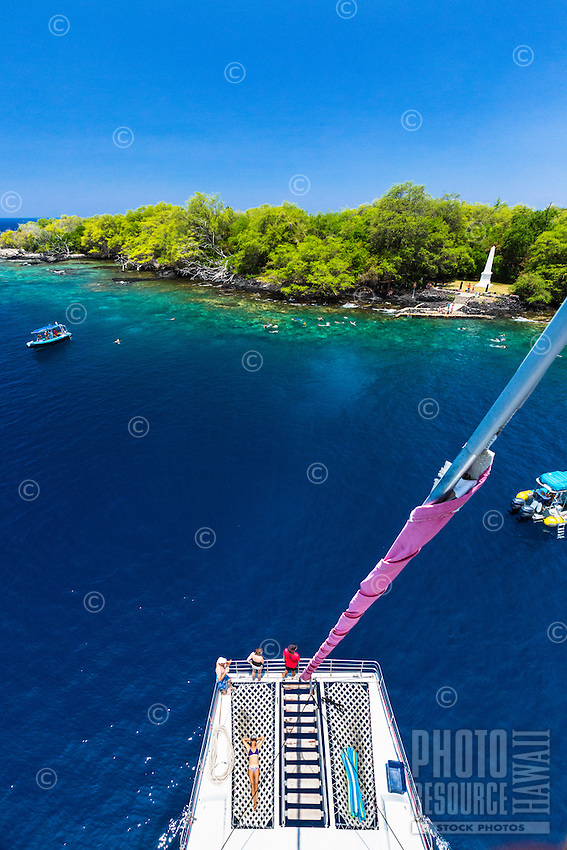 Tourists on a catamaran cruise marvel at the clear waters of Kealakekua Bay, Hawai'i Island.