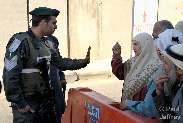 At a check point, Israeli soldiers prevent Palestinians from entering Jerusalem.