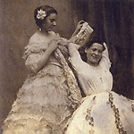 A well dressed young lady,  in evening dress, assists  another lady to dress. Her  camisole or possibly chemise  is clearly visible & her gown  is obviously in two parts.     Date: circa 1860