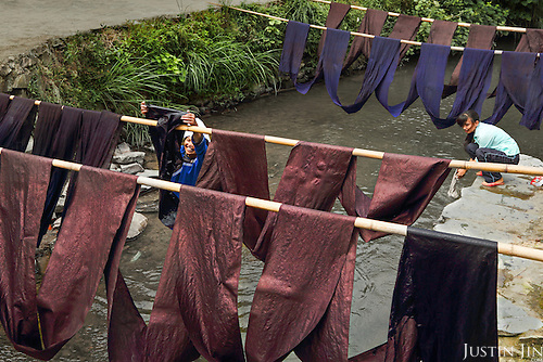 A Dong woman hangs freshly-dyed fabric along the river.