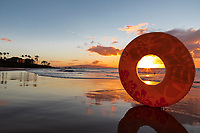 A young swimmer in the water is framed by an inner tube at sunset, Wailea Beach, Maui.