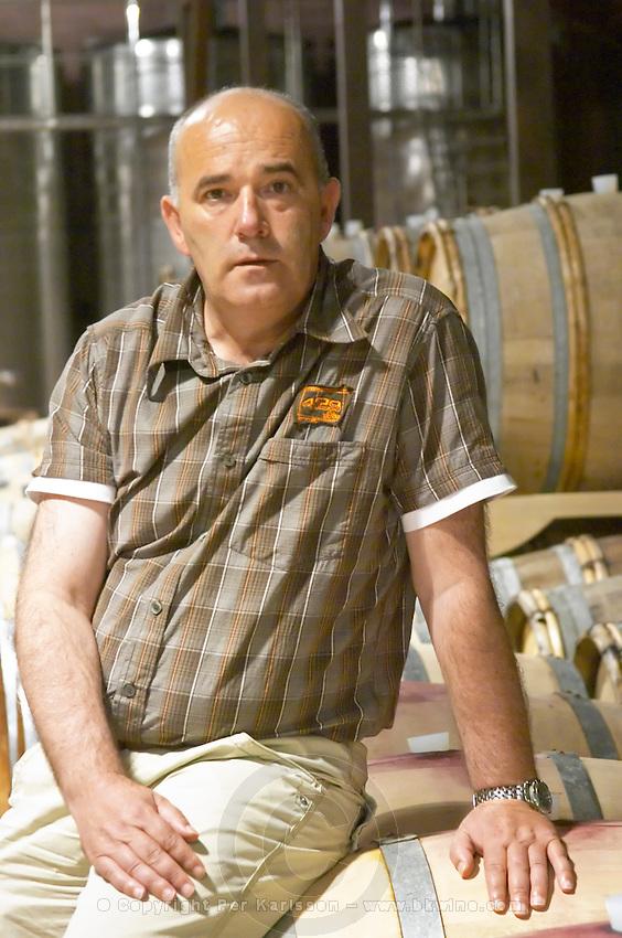 The owner and manager Cobroslav Barbaric sitting on an oak barrel in the winery. Hercegovina Produkt winery, Citluk, near Mostar. Federation Bosne i Hercegovine. Bosnia Herzegovina, Europe.