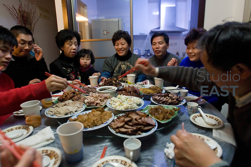 Chinese family members share Chinese New Year's Eve's dinner together, in Shanghai, China, on February 13, 2010. The Chinese New Year, or Spring Festival, is the most important Chinese holiday. It is the only occasion of the year when the whole family gets together, no matter what. And the most important part of Chinese New Year's Eve is the dinner every family has. Shared in a joyous atmosphere, the glorious dinner includes dozen of meals and lasts for hours. Chinese New Year's Eve is also the place for rituals: for instance, to burn offerings as gift to dead members of the family, or to offer 'red envelopes' full of crispy bank notes to younger generations. Photo by Lucas Schifres
