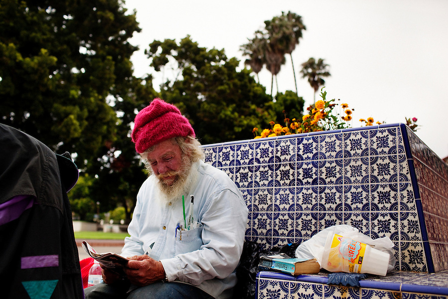 Ventura, California, July 20, 2010 - Mike Vance sits on a bench along Figueroa next to Mission Park in downtown Ventura reading a magazine. Mr. Vance has been homeless roughly since 1966, when he says he was crushed by a tree that left him unable to hold a steady job. He survives from small SSI checks and the kindness of the local Knights of Columbus Hall that allows him to sleep on their steps and occasionally feeds him. Mr. Vance likes to read and is often seen on these benches and in the neighboring park reading magazines and books people leave behind. Because of the public rest rooms in Mission Park as well as its proximity to the River it is a popular spot for the homeless in Ventura. .