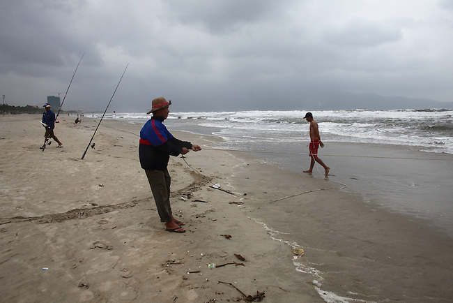 A fisherman hauls in a net on a stormy winter day in Da Nang, Vietnam. Dec. 23, 2012.
