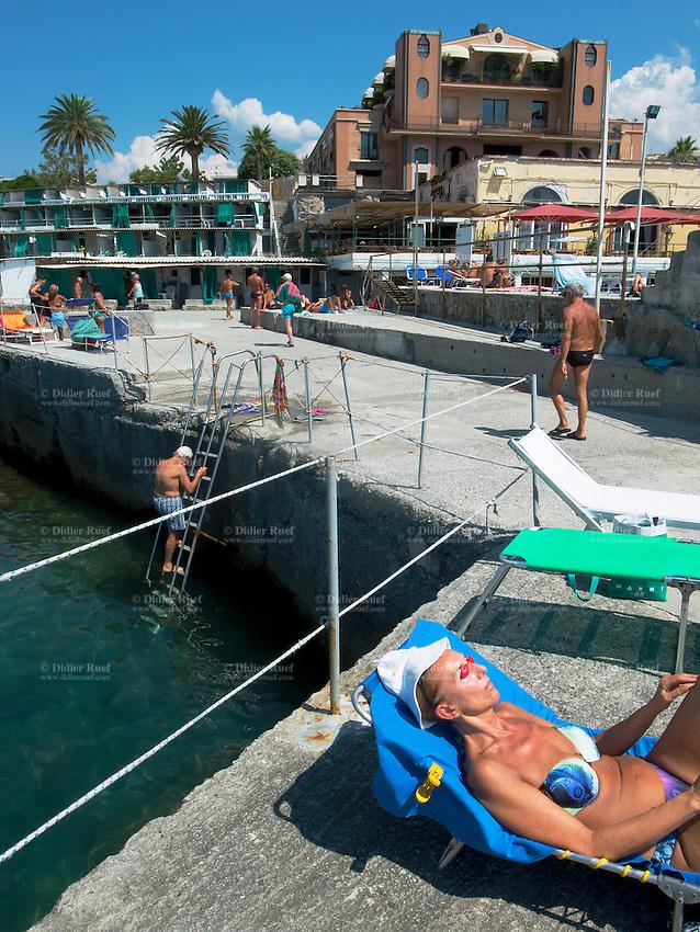 Italy. Liguria Province. Genova. Nuovo Lido beach resort. An elderly woman is sunbathing while people swim in the Mediterranean sea. 17.08.13 © 2013 Didier Ruef